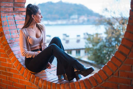 Caucasian brunette model sitting with the city in the background with a beautiful ponytail and a pink sweater. Street style fashion Standard-Bild