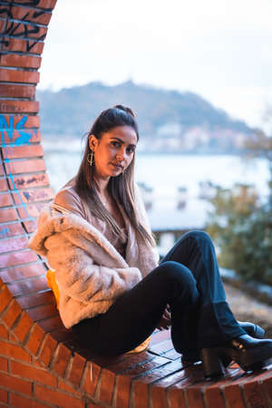 Caucasian brunette model sitting in winter with city in background. Street style fashion 免版税图像