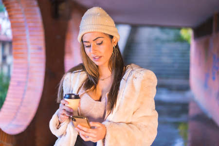 Young pretty Caucasian brunette in the city writing a message on the phone, wearing a pink wool sweater and hat. Street style fashion
