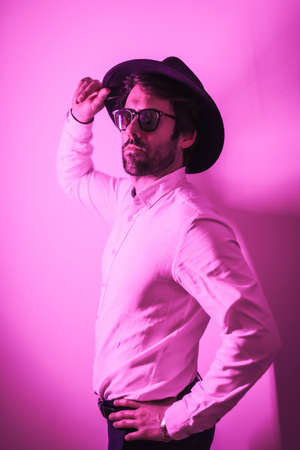 Studio lifestyle, a young Caucasian man with a seductive look in a photo session with sunglasses, with neon pink light Banque d'images