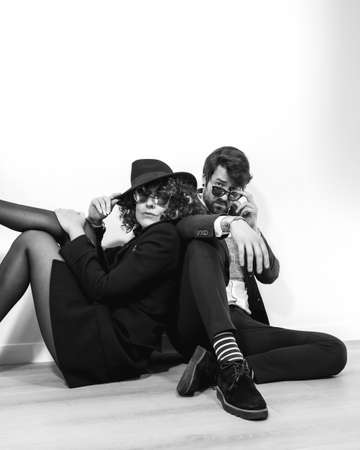 A Caucasian couple sitting on the floor in a black and white fashion shoot, wearing stylish suits and sunglasses