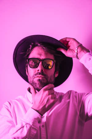 Studio lifestyle, a young Caucasian man with a seductive look in a photo session with sunglasses, with neon pink light 版權商用圖片