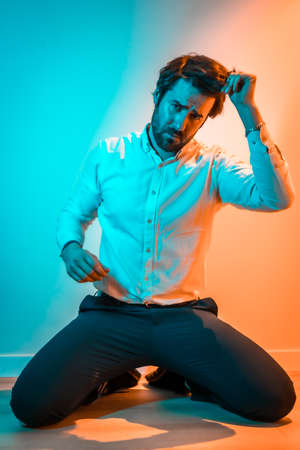 Lifestyle studio, a Caucasian man on his knees wearing a white shirt, illuminated with an orange and blue neon light 版權商用圖片