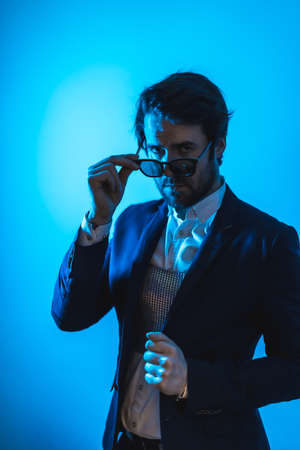 Studio lifestyle, a handsome young Caucasian man in a session with elegant clothes and sunglasses, with neon blue light