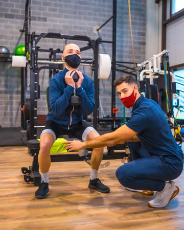 Personal trainer in the gym correcting the athlete's squats in the  pandemic, a new normal. With protective face mask 版權商用圖片