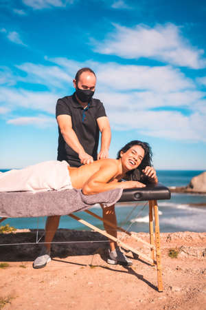 Massages on the coast near the sea, masseuse with face mask in the pandemic