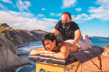 A young man performing a massage in nature on the coast near the sea, a dream come true, masseuse with face mask in the pandemic