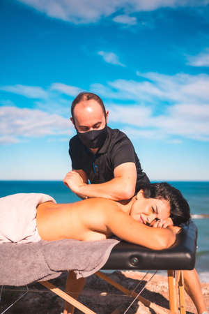 Enjoying massages on the coast near the sea, masseuse with face mask in the pandemic
