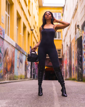 Urban style of a fashionable black girl in a black suit and high boots