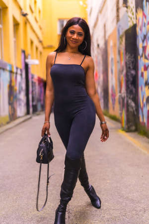 Fashionable urban style with a black African girl in a black suit and high boots on a city street. Smiling with a black bag