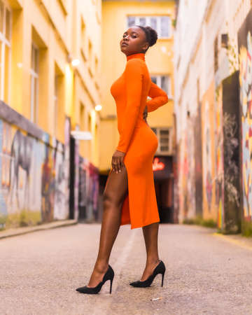Fashionable urban style with a black African girl in an orange dress and black heels on a city street. Standing pose with seductive gaze