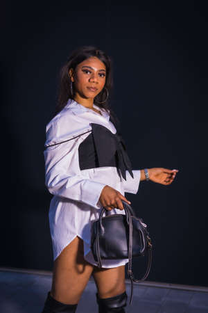 Urban style fashion with a black African girl on a city street at night. With white shirt on a white background and a black top