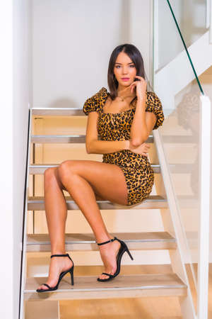 Caucasian girl in a tight dress with leopard print sitting on the stairs of a hotel, posing in fashion