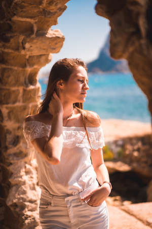Lifestyle of a young red-haired caucasian girl dressed in white next to a rocks near the sea