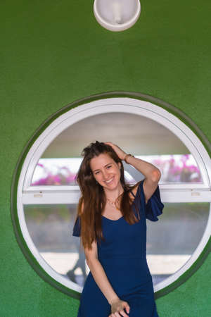 A young redhead Caucasian girl smiling sitting in a blue dress next to a white door of a green house
