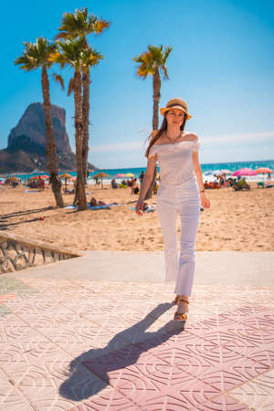 A Caucasian redhead dressed in white and with a straw hat walking along the beach of Calpe in summer, Valencia. Spain 版權商用圖片