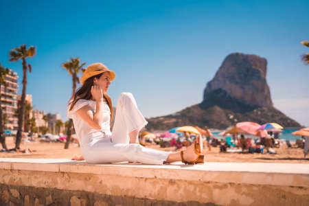 Lifestyle of a young red-haired Caucasian girl dressed in white and with a straw hat on the beaches of Calpe, Valencia. Spain