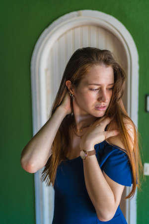 Lifestyle of a young red-haired caucasian girl in a blue dress in a summer perched next to a white door of a green house