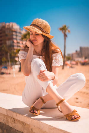 A Caucasian redhead dressed in white and with a straw hat on the beaches of Calpe, Valencia. Spain. Enjoying the Mediterranean Sea