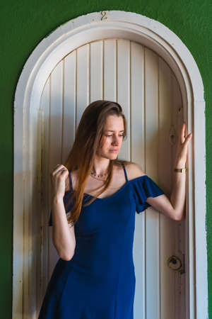 A young red-haired caucasian girl in a blue dress next to a white door of a green house, vertical photo