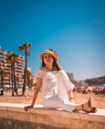 Lifestyle of a young red-haired Caucasian girl dressed in white and with a straw hat on the beaches of Calpe, Valencia. Spain. Enjoying the Mediterranean Sea 版權商用圖片