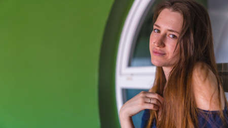 A smiling young pretty redhead Caucasian woman sitting in a blue dress next to a white sale of a green house, copy space and paste