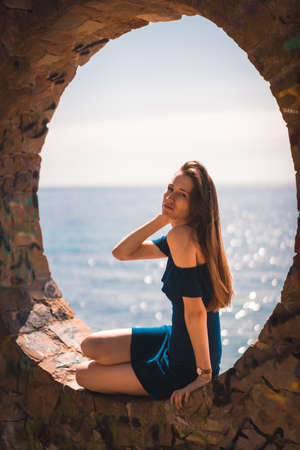 Lifestyle of a young pretty red-haired Caucasian woman sitting in a blue dress by the sea, in a stone window 版權商用圖片