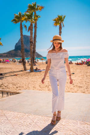 A red-haired Caucasian dressed in white and with a straw hat in the town of Calpe, Valencia. Spain. Enjoying the summer in the Mediterranean Sea
