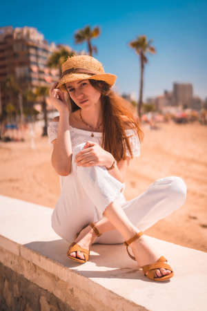 A young red-haired Caucasian girl dressed in white and with a straw hat on the beaches of Calpe, Valencia. Spain. Enjoying the Mediterranean Sea