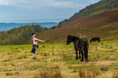 A young man with a wild black horse on top of Mount Adarra in the town of Urnieta near San Sebastian, Gipuzkoa. Basque Country
