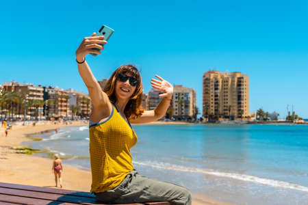 A young woman taking a selfie on the Cura beach in the coastal city of Torrevieja, Alicante, Valencian Community. Spain, Mediterranean Sea