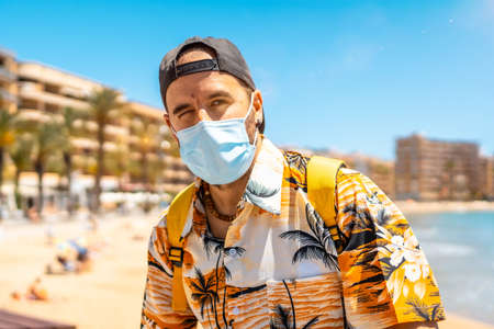 A young man with a tourist surgical mask on the Cura beach in the coastal city of Torrevieja, Alicante, Valencian Community. Spain, Mediterranean Sea Foto de archivo