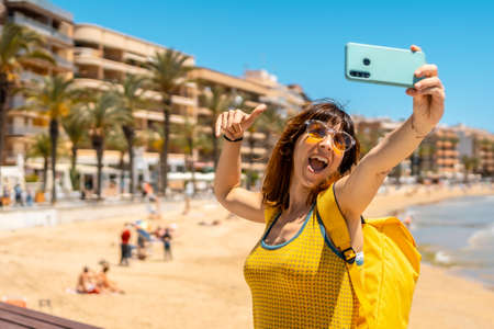 A young tourist taking a selfie with the phone at Playa del Cura in the coastal city of Torrevieja, Alicante, Valencian Community. Spain, Mediterranean Sea