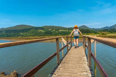 A young woman on the wooden piers of the Urdaibai marshes, a Bizkaia biosphere reserve next to Mundaka. Basque Country