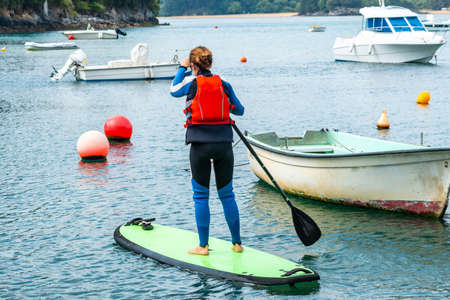 A young woman paddle surfing in the sea in Urdaibai, a Bizkaia biosphere reserve next to Mundaka. Basque Country