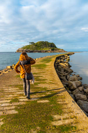 A young tourist on the footbridge to go to San Nicolas Island at low tide from Isuntza beach in Lekeitio, Basque Country. Bay of Biscay. Spain