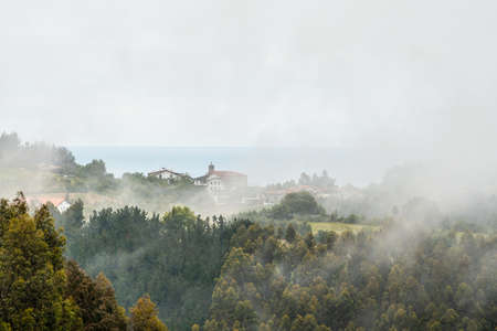 A small town on top of the mountain full of mist. Spring in Ispaster next to Lekeitio, landscapes of Bizkaia. Basque Country