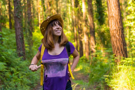 Traveler woman smiling with hat and looking at the forest pines, hiker lifestyle concept, copy and paste space, Basque Country forests. Spain 版權商用圖片