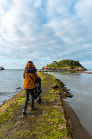A mother with her son on the footbridge to go to San Nicolas Island at low tide from Isuntza beach in Lekeitio, Basque Country. Bay of Biscay. Spain