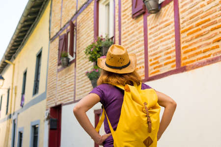 Lifestyle, an adventurous hiker with a yellow backpack visiting a traditional rural village, copy and paste space, Municipality of Ea in the Basque country. Spain