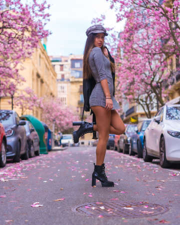 Brunette Caucasian girl walking in the city with the flowered trees in spring 版權商用圖片