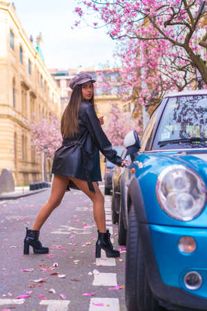 Street Style in the city, brunette Caucasian girl in a leather jacket and a beret, getting into her blue car in the city with the blossoming trees in spring