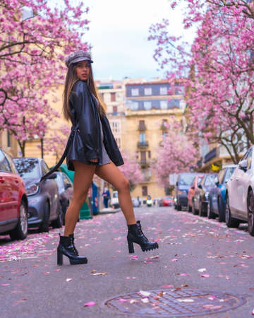 Street Style in the city, brunette Caucasian girl walking in the city with the flowered trees in spring