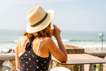Summer vacation lifestyle. Young caucasian girl in a hat having a soda next to the beach and looking at the sea