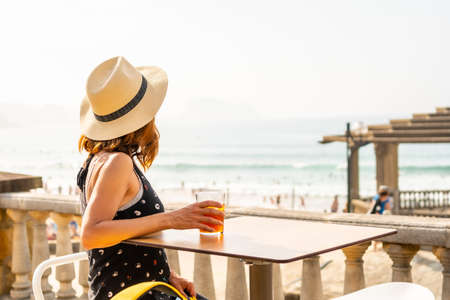 Summer vacation lifestyle. Young caucasian girl in a hat having a soda next to the beach