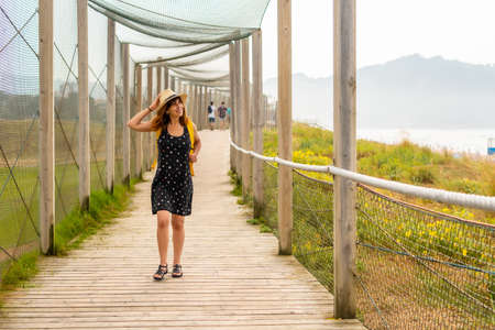 Summer vacation lifestyle. Young and adventurous Caucasian girl enjoying the summer walking alone along the beach 版權商用圖片