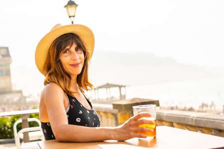 Summer vacation lifestyle. Portrait of a young Caucasian girl with a hat having a soda next to the beach 版權商用圖片