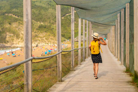 Young and adventurous girl enjoying summer vacation walking alone along the beach 版權商用圖片