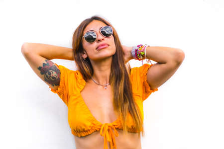 Lifestyle of a young caucasian brunette with orange t-shirt, sunglasses and short pants on a white background, with copy space and sticks 版權商用圖片