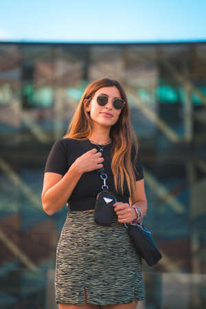 Beautiful young caucasian brunette businesswoman outside the green glass office building background. With sunglasses and looking 版權商用圖片